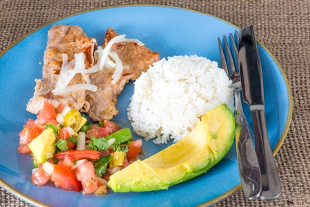 a portion: Latin American cuisine fusion: pork steak, white rice,pico de gallo and avocado.Mexican and Cuban cuisine fusion produces a healthy balanced plate of food