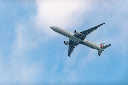 preferred: Air Canada Airplane in the distance flying in blue skies, Canadas most preferred airline Editorial