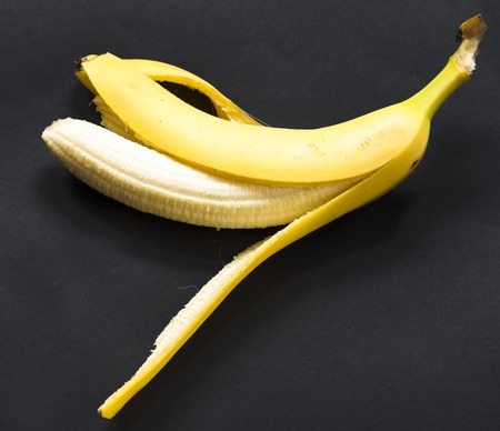 Benefits of banana fruit over black background: The fruit has a lot of potassium which is helpful in maintaining blood pressure. Stock Photo