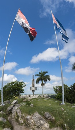 julio: Loma del Capiro or Capiro Hill monument featuring the Cuban flag and the flag of the July 26 Movement flying in a blue sky
