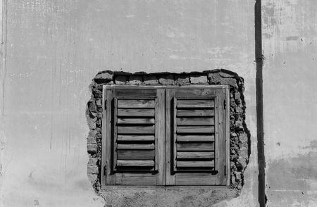 craked: Housing conditions: Old wooden window installed in a craked wall. Stock Photo