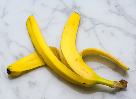 loosely: Yellow banana peel over floor marble surface. Loosely dropped this peel can be a slippery danger.