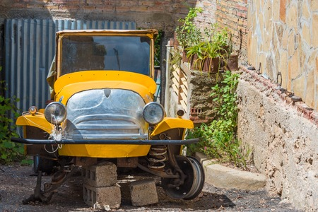 rudimentary: Old rare vintage car reparation in alley between two houses. This car might be used as tourist taxi in the future. Cubans allot a lot of value to old cars spending many time in reparation efforts. Stock Photo