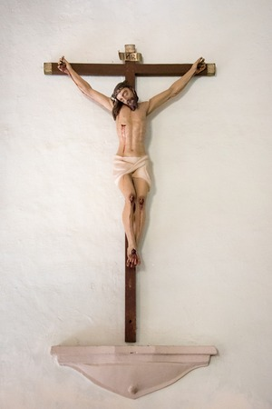 crucify: Bleeding Jesus Christ on the cross. Figurine nailed to the wall of a believer house. Passion of Christ Stock Photo