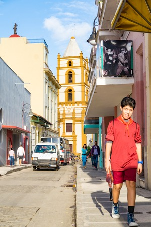 everyday: Cuban pioneer in sidewalk, Catholic church in background and the everyday traffic in the city downtown