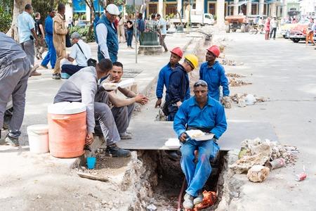 taking a break: Old Havana reconstruction: Construction workers having lunch and taking a break