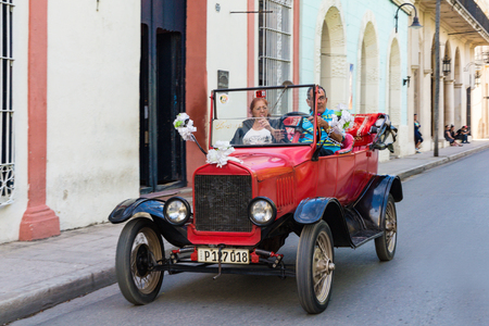 driven: Vintage red American convertible car, driven by tourist in Camaguey. 1910s vehicle Editorial