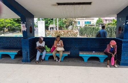 old bus: Women sitting at old bus stop: Waiting for bus o arrive.
