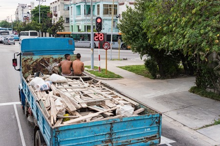 clutter: Unsafe practices:Old truck carrying wooden boards and two young men sitting on top of clutter.