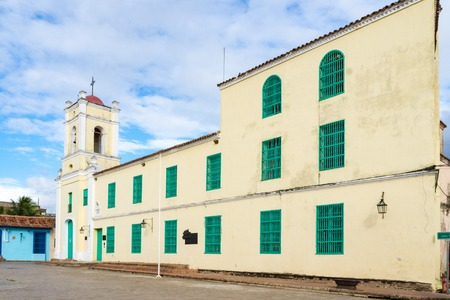 colonial church: Catholic church in Plaza de San Juan de Dios. Spanish colonial church, vintage tiled roof also painted light yellow with green doors and windows. Editorial