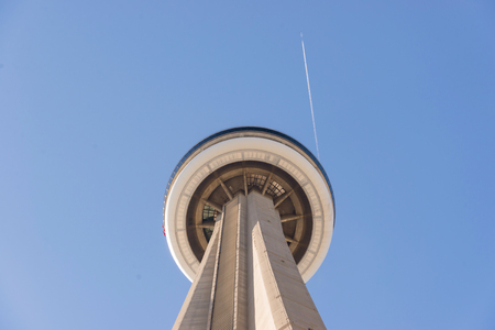 passing over: CN tower or Canadian National tower with jet passing over a blue sky