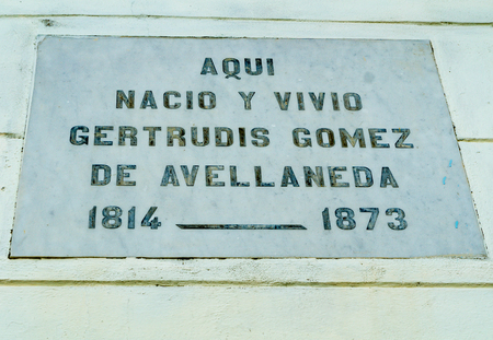 gomez: Gertrudis Gomez vintage blue house with wooden door and windows.