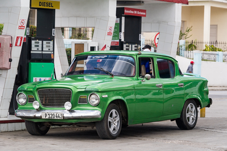 means of transportation: Socialist Cuba transportation means: Old green American car parked at a fuel station. Old vehicles are a tourist attraction in the tropical island.