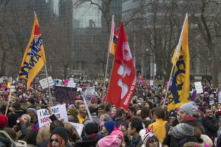 marched: Union flags waving in crowd. Women and their allies marched in support of the Womens March in Washington.   Toronto city saw one of the largest events on its history as thousands of people protested the Donald Trump stances. Editorial