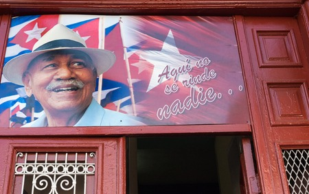 Juan Almeida Bosque photo at entrance of Cuban building. He was a Cuban Revolution Commander who in the middle of a combat yelled to his comrades: Nobody Surrender Here and a four letter word. The phrase became an icon of the Cuban bravery.