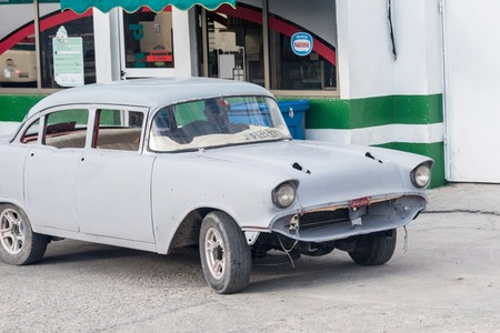 Old classic American car in Cupet service station. The vehicle is undergoing body repairs.