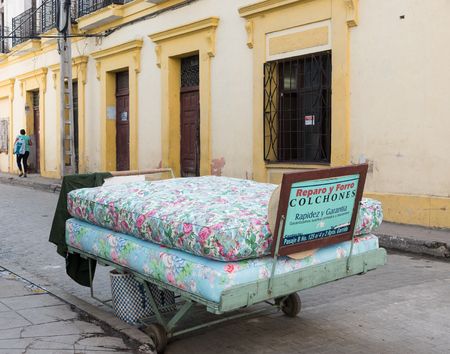 Mattresses on trailer with Spanish sign reading I repair mattresses. After economic changes, self employment has become an important source of work in Cuba
