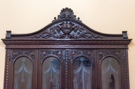 Spanish colonial furniture. Antique polished wooden cabinet with very fine ornate carving.