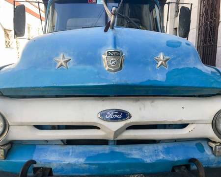 holguin: Front of vintage Ford blue and white truck. Old obsolete American trucs and cars still working are a major tourist attraction in the Caribbean Island.