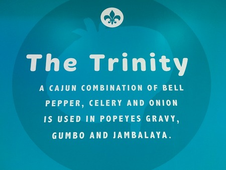 Popeyes Louisiana kitchen sign explaining the process of their plates. Turquoise blue trinity sign with a combination of Cajun ingredients written. Imagens