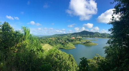Aerial view of Hanabanilla lake or dam.  The tropical area is a Natural Reserve and used for Eco-tourism in the Caribbean Island. View of bay with blue sky, and clouds in background.