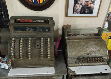 cash register building: Antique cash registers on a wooden table. The items are conserved at the house of Cuban artists Ileana Sanchez and Joel Jover. Note the photo of Jill Tracy Biden in the wall from when she visited the artists. Editorial