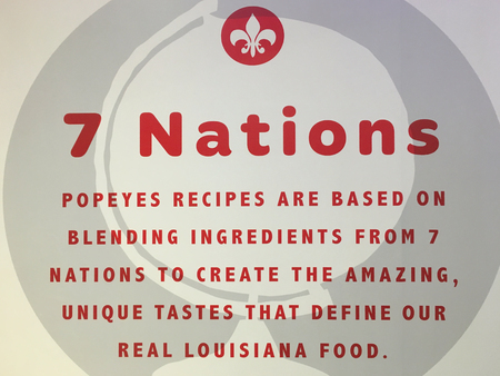 Popeyes Louisiana Kitchen information sign in restaurant. They explain the origin of their ingredients. Editorial