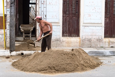 Cuban real people man construction worker: Mason helper filling a cart with construction sand using shovel.