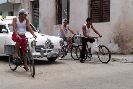 the archaic: Studebaker car and bicycles in a Cuban urban intersection. Socialist Cuba transportation. Archaic model car moving on street along with cyclists.