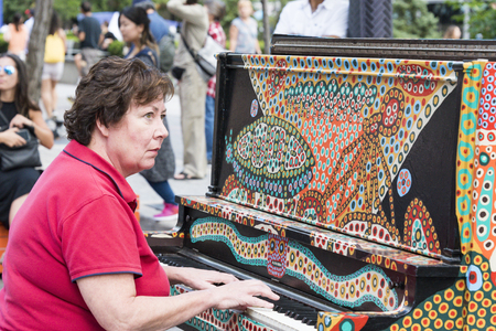 colorfully: Canadian street festivals: Lady playing a colorfully designed piano in a public place. Summer multicultural festivals are a major tourist attraction in Toronto