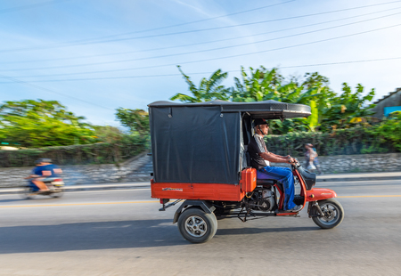 Cuban tricycles or motonetas in action. The vehicle is used as a private small business for transporting people inside the city. Editorial
