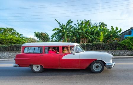 Old obsolete American red and gray car used for self employment in the Caribbean island. After economic changes, car owners can use them as taxis in urban areas Editorial
