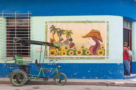 Beautiful urban art mural in old building and Cuban everyday lifestyle. Tricycle or bicitaxi waiting for passengers while people chat at the door.