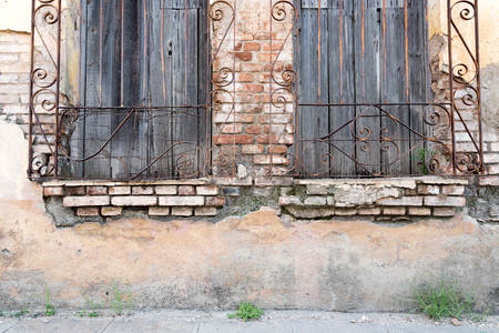 Cuban colonial weathered architecture details. Wooden windows with iron guard in house facade. Economic hardship has forced many people to keep their property without maintenance. Stock Photo