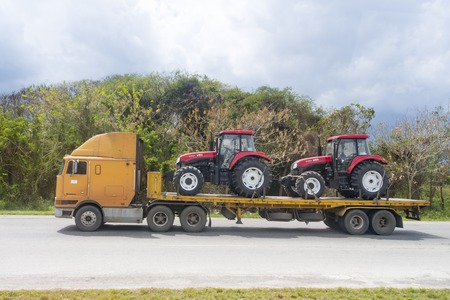 Cuba economic recuperation: new imported agricultural tractors are transported in truck at the National Highway Redakční