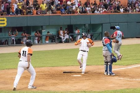 General scene of Cuban baseball or National Series. Game between 'Villa Clara' and 'Ciego de Avila' teams at the Sandino Stadium. Scoring a run at home plate.