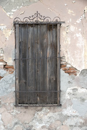 Cuban old weathered and worn out architecture. Colonial wooden window with iron guard.  Results of economic hardship on real estate.