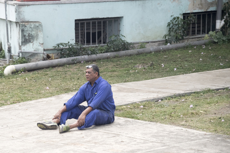 Man in overall sitting in the sidewalk. Real Cuban people lifestyle at the entrance of Havana city, the Cuban capital.