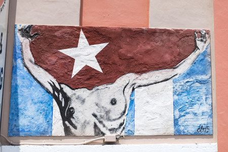 Symbols of the Cuban exiles and immigrants nostalgia in Little Havanas Calle Ocho. Urban work of art showing the torso of a man carrying the Cuban flag. Editöryel