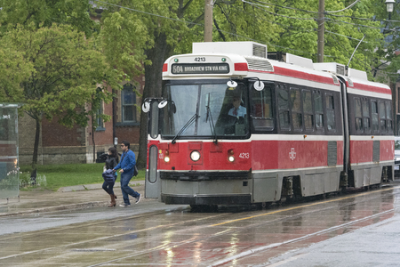 Old vintage Bombardier streetcar working the route of King Street East on a rainy day. The public transportation vehicles are being replaced gradually for newer ones