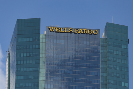 headquartered: Wells Fargo sign or logo on top of glass tower in downtown Miami.   Wells Fargo & Company is an American international banking and financial services holding company headquartered in San Francisco, California, with hubquarters throughout the country. It
