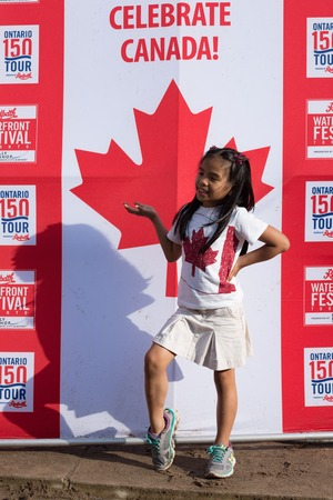 Canada Day 150th Anniversary of confederation.  Female child or immigrants having fun and having her picture taken in banner in Little Beach