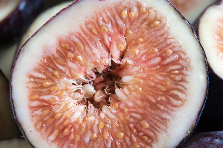 Common fig fruit, close up of a transversal cut of the sweet delicacy. Benefits of the fig include being rich in dietary fiber and manganese