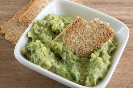 Guacamole, close up of the traditional Central American spread food. Guac is an avocado-based dip, or salad first developed by the Aztecs in what is now Mexico