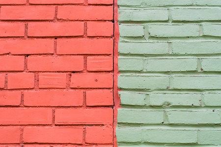 Dual toned brick wall, half of it is brick red and half is light green. Colour contrasts in old buildings. Фото со стока