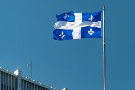 ケベック州旗が青い澄んだ空で手を振っています。