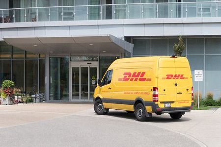 Yellow DHL delivery van, stopping outside a gray colored commercial building. Editorial