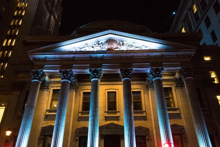 Bank of Montreal facade at night. The oldest bank of Canada is illuminated with blue and yellow lights.