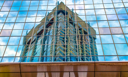Reflection of a modern downtown building on a glass wall. The area is a tourist attraction in the Canadian city. Редакционное