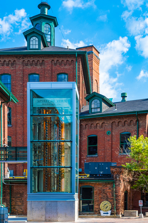 Distillery District contrast of a glass exhibit with the old red brick buildings. The famous place is a declared heritage area and a tourist attraction in the city